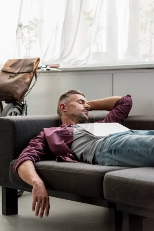 Photo for Man laying on sofa with laptop and sleeping at home office - Royalty Free Image