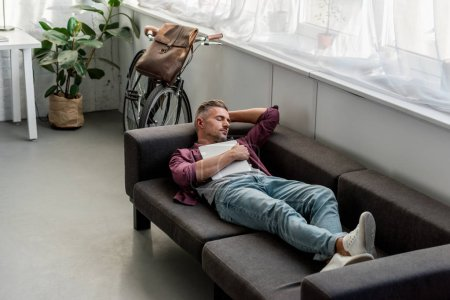 Photo for Tired man laying on sofa with laptop and sleeping at home office - Royalty Free Image
