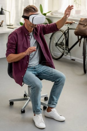 Photo for Man sitting on chair and gesturing in virtual reality headset at home office - Royalty Free Image