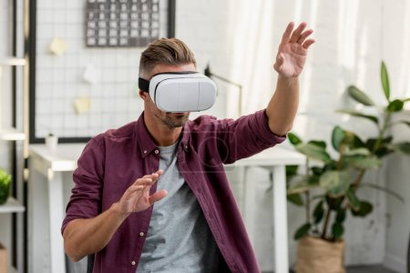 man gesturing in virtual reality headset at home office