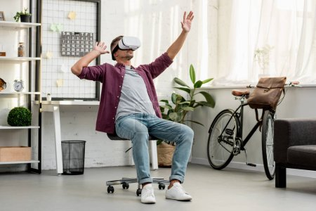 man sitting on chair and gesturing in virtual reality headset at home office
