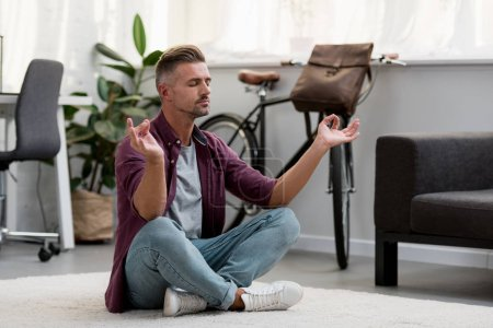 Photo for Concentrated man sitting on floor practicing yoga at home office - Royalty Free Image