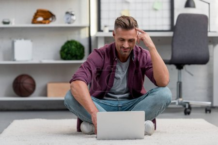 Photo for Handsome man sitting in home office and working on laptop - Royalty Free Image