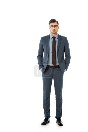 adult handsome businessman standing with hands in pockets isolated on white