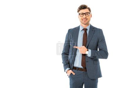 Photo pour Homme d'affaires souriant en lunettes et costume pointant latéralement isolé sur blanc - image libre de droit