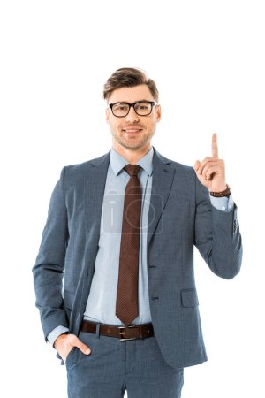 cheerful businessman in glasses and suit pointing upwards isolated on white