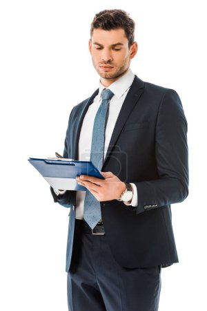 concentrated businessman in suit looking at clipboard isolated on white