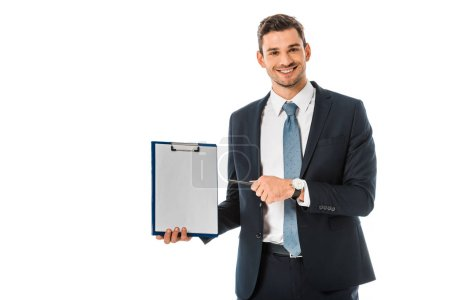 smiling businessman in suit pointing at empty clipboard isolated on white