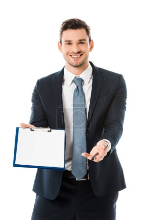 smiling businessman in suit showing empty clipboard and pen isolated on white