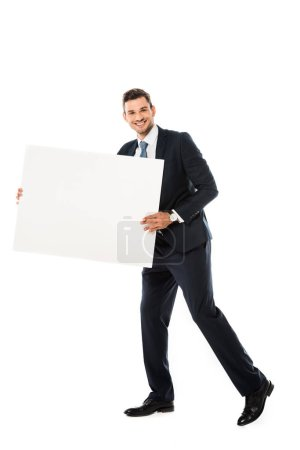 smiling businessman in suit showing blank poster with copy space isolated on white