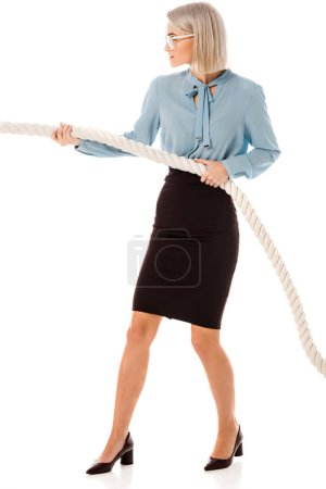 Photo for Concentrated beautiful businesswoman pulling rope isolated on white - Royalty Free Image