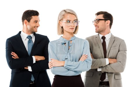 cheerful businessmen standing with arms crossed behind serious businesswoman isolated on white