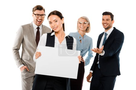 Photo for Beautiful businesswomen holding empty placard while colleagues standing behind isolated on white - Royalty Free Image