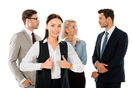 successful businesswoman showing thumbs up and standing with colleagues isolated on white