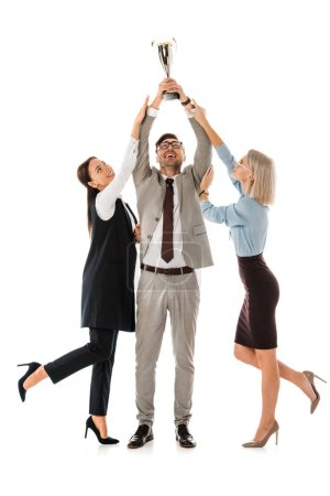 successful businessman holding up trophy cup while female colleagues trying to get it isolated on white
