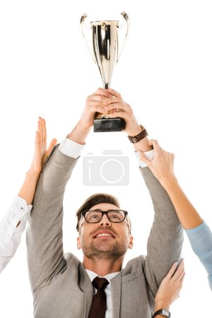 successful businessman holding trophy cup above the head while colleagues trying to get it isolated on white