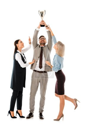 handsome businessman holding up award while female colleagues trying to get it isolated on white