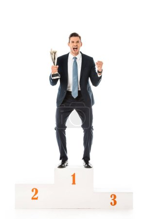 Photo for Excited emotional businessman with trophy cup standing on winners podium isolated on white - Royalty Free Image