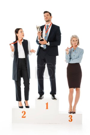 businesspeople holding awards while standing on winners podium isolated on white