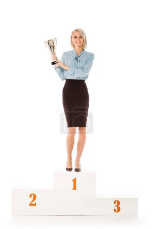 Photo for Successful businesswoman with trophy cup standing on winners podium isolated on white - Royalty Free Image