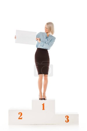 Photo for Beautiful blonde businesswoman holding blank placard while standing on winners podium isolated on white - Royalty Free Image