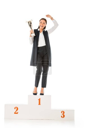excited business winner holding trophy cup while standing on winners podium isolated on white