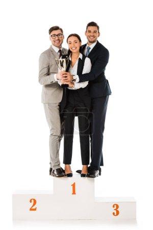 Photo pour Équipe des activités tenant le trophée Coupe en se tenant debout sur le podium de gagnants ensemble isolé sur blanc - image libre de droit
