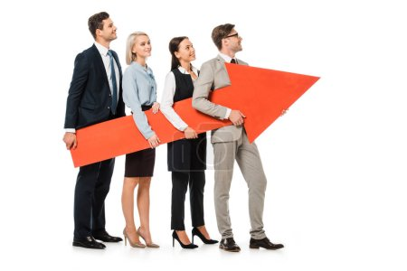 young smiling businesspeople holding big red arrow together isolated on white