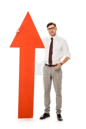 young handsome businessman standing with big red arrow isolated on white