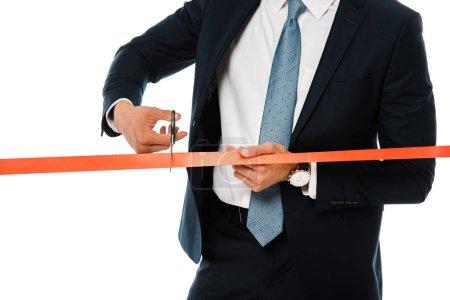 Photo pour Vue recadrée de femme d'affaires, coupe le ruban rouge avec des ciseaux pour l'inauguration, isolé sur blanc - image libre de droit