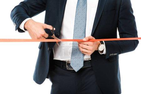 Photo pour Vue recadrée d'homme d'affaires, coupe le ruban rouge ou une bande avec des ciseaux pour l'inauguration, isolé sur blanc - image libre de droit