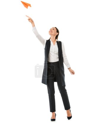 attractive businesswoman throwing paper plane, isolated on white