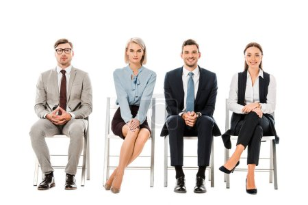professional businesspeople sitting on chairs and looking at camera isolated on white