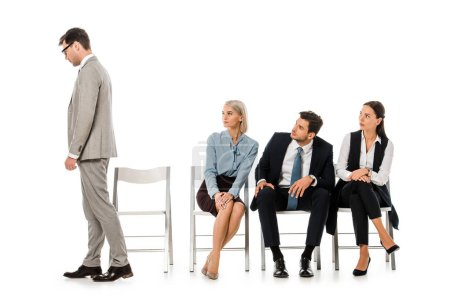 fired businessman going away while colleagues sitting on chairs and looking at him isolated on white
