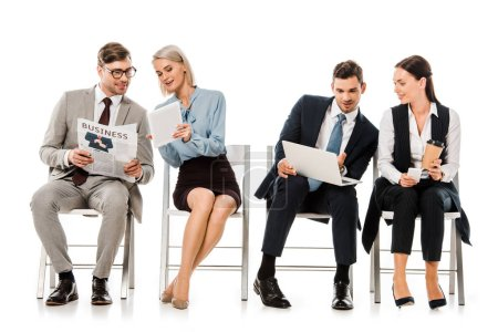 businesspeople sitting on chairs and discussing work with digital devices, isolated on white