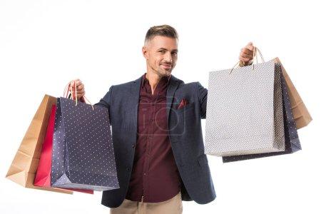 Photo pour Adulte mâle shoppper en veste montrant des sacs en papier coloré isolé sur blanc - image libre de droit