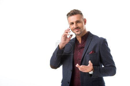 Photo for Joyful stylish man gesturing by hand while talking on smartphone isolated on white - Royalty Free Image