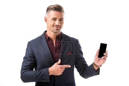 positive adult stylish man in jacket pointing by finger at smartphone with blank screen isolated on white