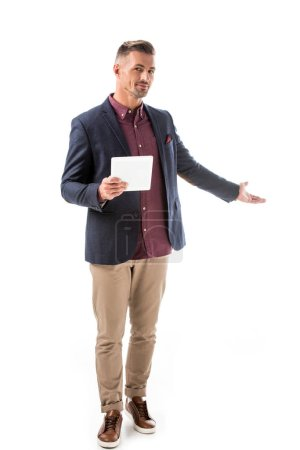handsome stylish man in jacket holding digital tablet and doing invite gesture isolated on white