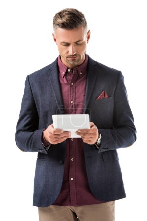 focused stylish man in jacket using digital tablet isolated on white