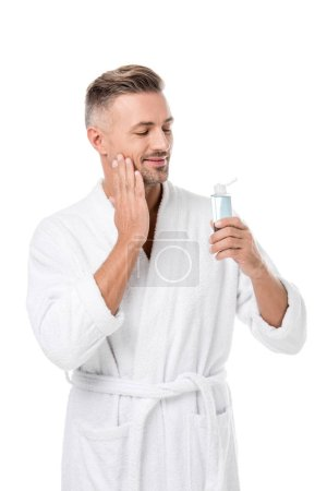 happy handsome adult man in bathrobe using shaving lotion isolated on white