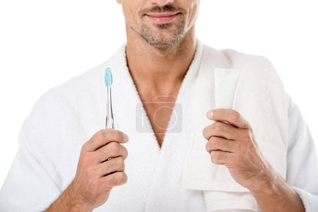 partial view of man in bathrobe with towel over shoulder holding toothpaste and toothbrush isolated on white