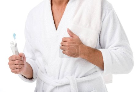 cropped image of man in bathrobe with towel over shoulder holding toothpaste and toothbrush isolated on white