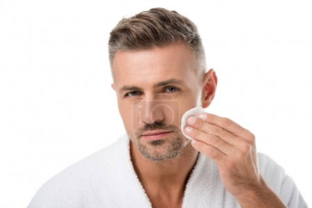 portrait of handsome man in bathrobe applying tonic by cotton pad on face isolated on white
