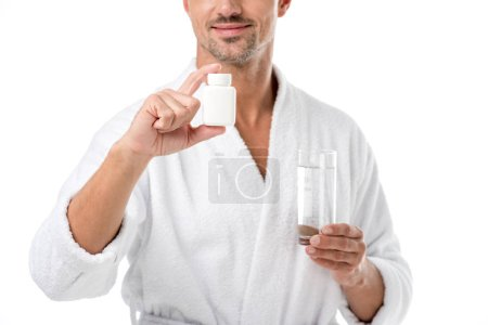 partial view of adult man in bathrobe showing vitamins and holding glass of water isolated on white