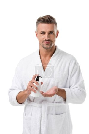 cheerful adult man in bathrobe using body lotion isolated on white