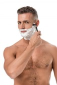 muscular shirtless man with foam on face shaving with razor isolated on white