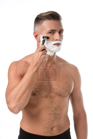 serious muscular shirtless man with foam on face shaving with razor isolated on white