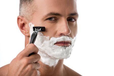 close up portrait of man with foam on face shaving with razor isolated on white