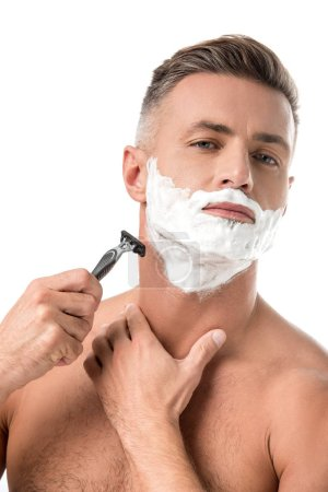 confident man with foam on face shaving with razor isolated on white